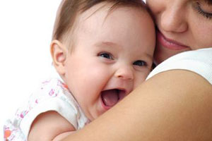Happy_infant_being_held_by_women_300_Pixels